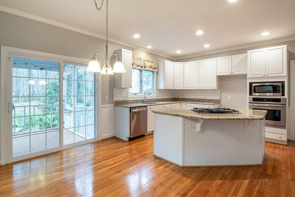 A kitchen with hard wood floors and a large window
